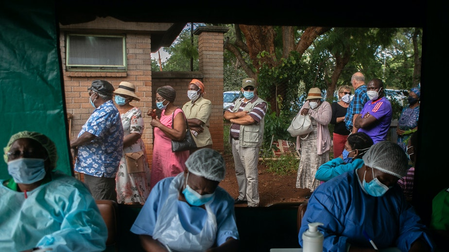 People wait outside a medical tent to receive a COVID-19 vaccine at a hospital in Harare, Zimbabwe, on March 29, 2021.