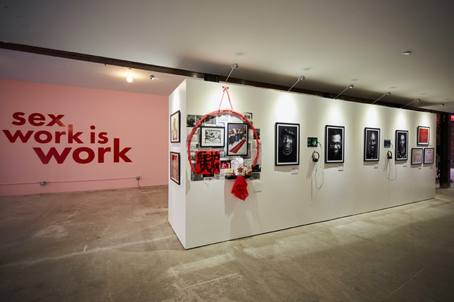 View of art exhibition with the words; Sex Work is Work, on the wall