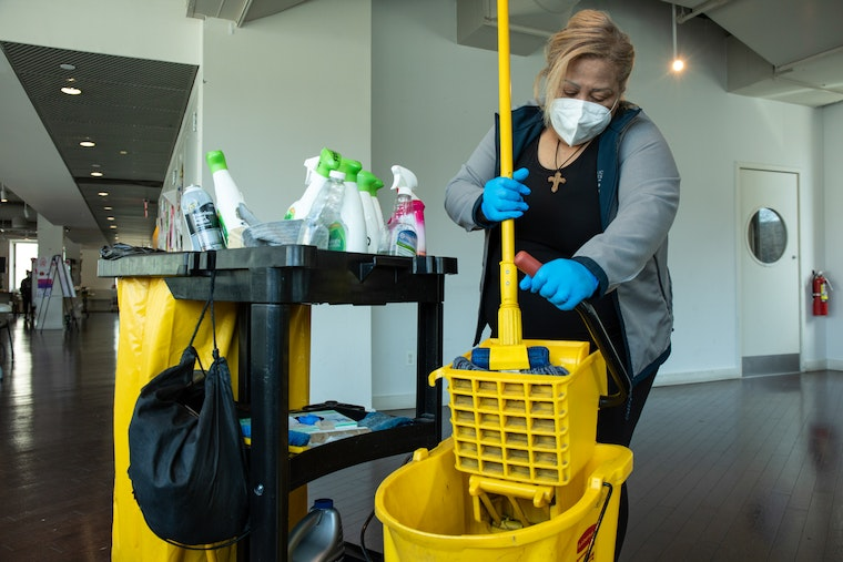 A woman wringing out a mop in a hallway