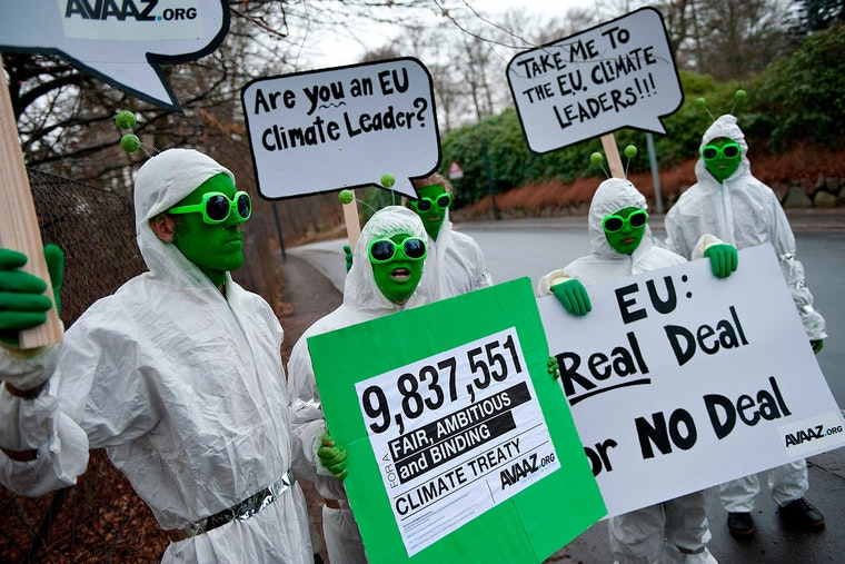 People wearing green face paint and costume antennae holding signs