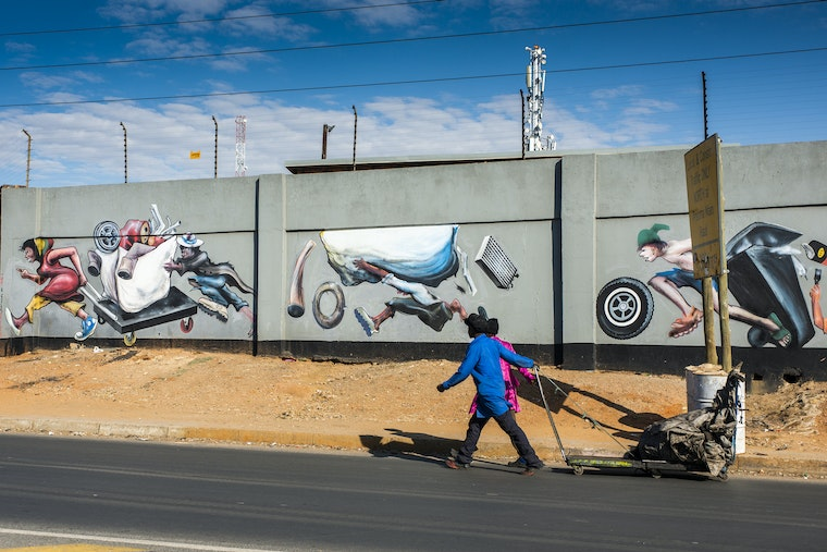 Trash pickers pull a cart past a mural