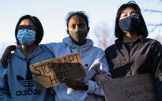 Three people attending a rally while wearing protective face masks