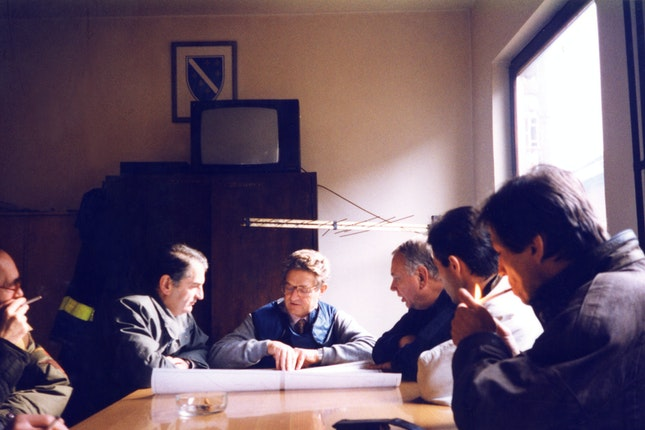 George Soros with a group of people looking over plan drawings