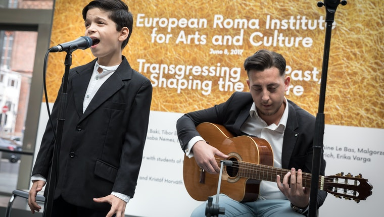 A boy singing next to a man playing guitar