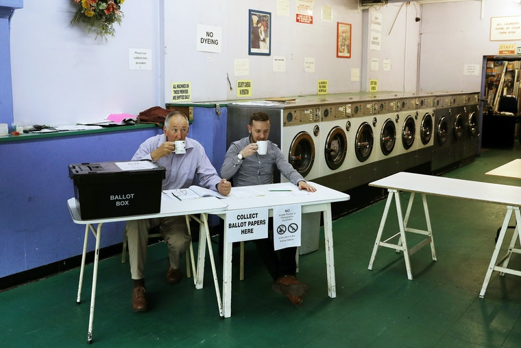 Two people sit at a polling table in a laundromat