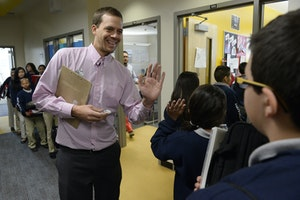 Teacher with his palm up in front of a line of students