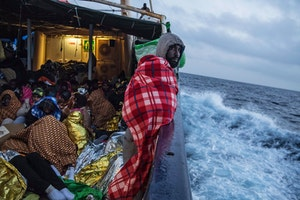 People wrapped in blankets on a ship at night
