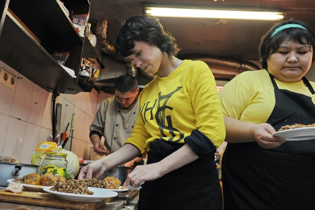 People in yellow shirts create plates of regional cuisine in the kitchen of a café.