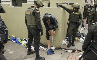 A man putting on a sock and surrounded by police officers