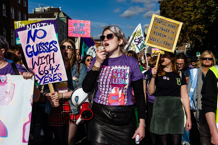 People in purple shirts at a protest in support of reproductive rights.