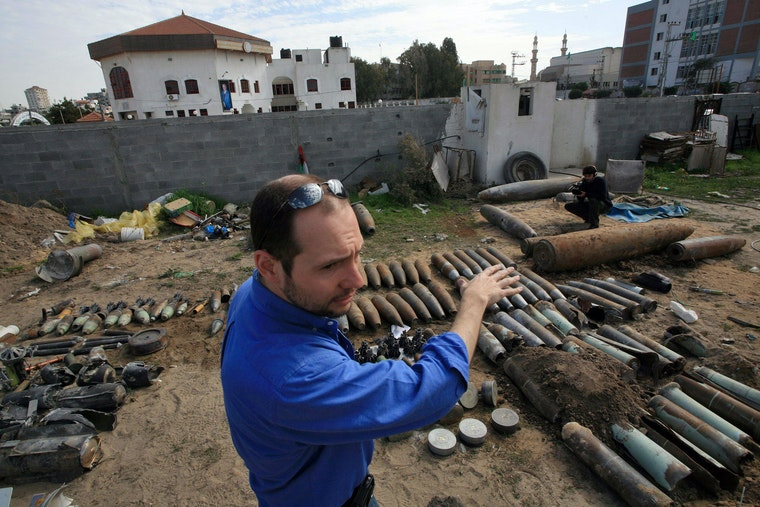 A man stands outside, in front of an assembly of used weaponry.