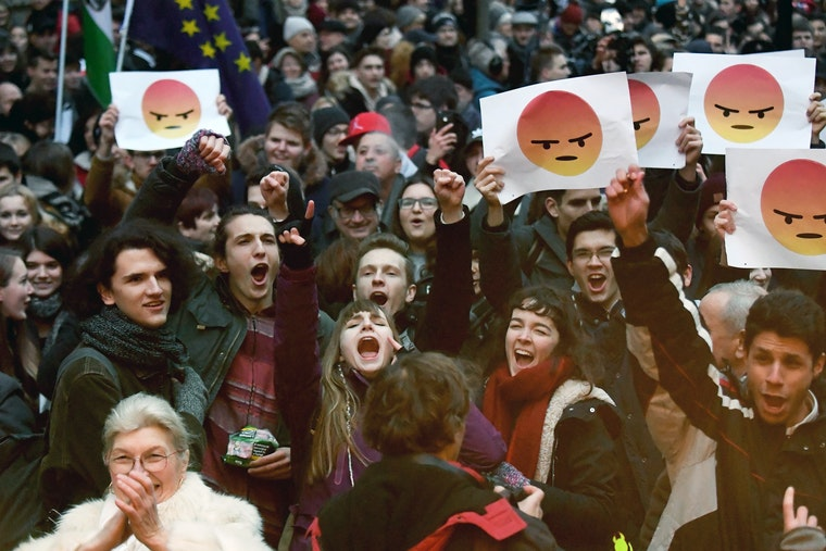 A crowd of young people stand outside in the cold while raising signs featuring an illustrated cartoon face that is supposed to represent anger.