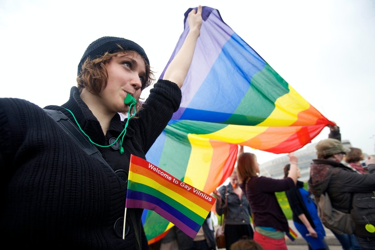 A young woman holds a rainbow flag above her head.