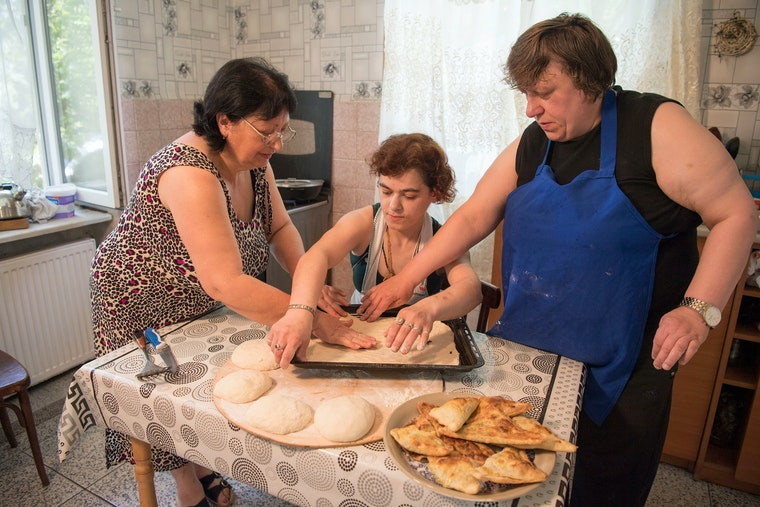Three women work together in a kitchen to bake some pies.