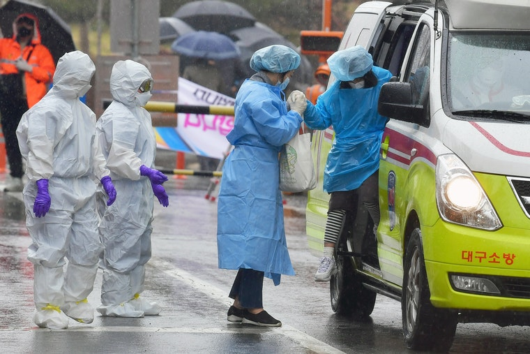 Nurses standing next to an ambulance in the rain