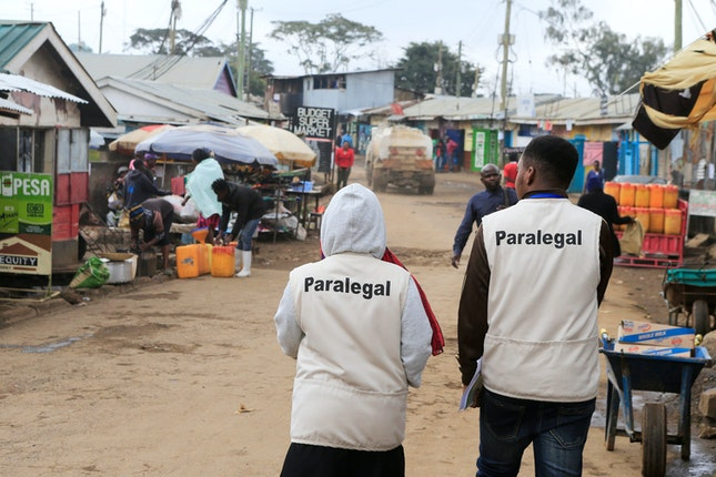 "A man and a woman wearing vests that say ""paralegal"" walking down a road."