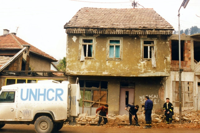 A UNHCR truck next to workers digging a trench