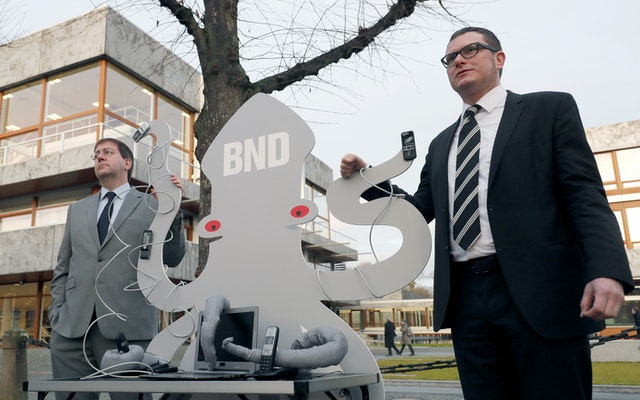 Two people stand with a grey octopus cutout balancing mobile phones