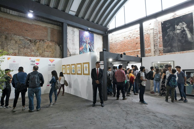 People and art work in a warehouse gallery space