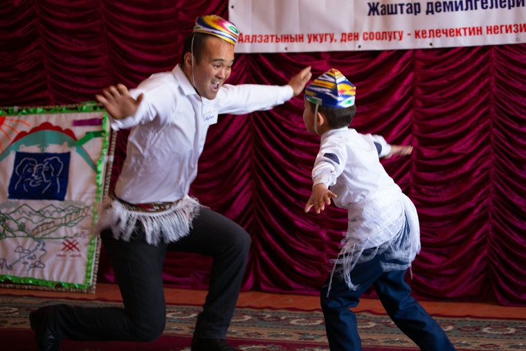 A man and a child dancing on a stage