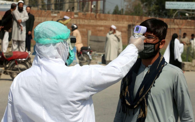 A person wearing protective gear points a thermometer at a man