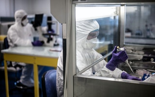 Two people in full-body protective gear in a laboratory