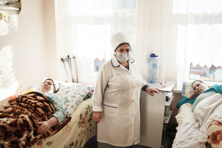 A nurse stands between two patients in beds in a hospital room