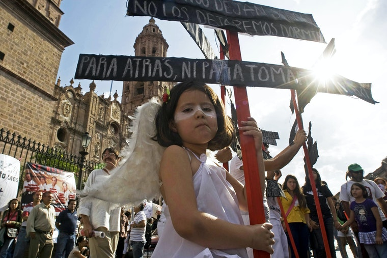 A young girl dressed as an angel at a rally