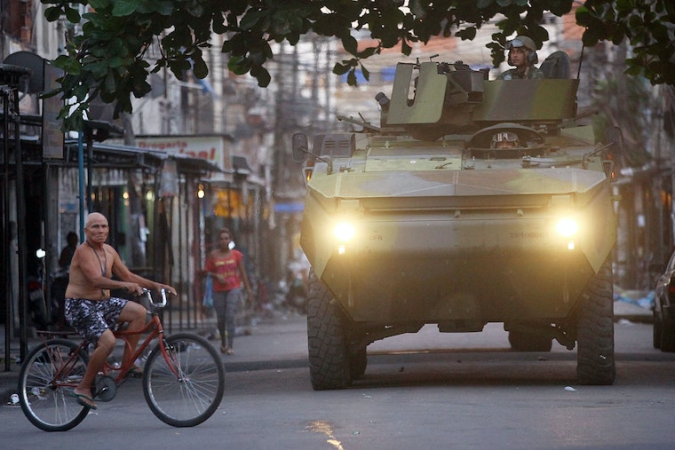 A man rides a bicycle in front of a military tank