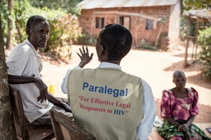 Paralegal talking with a family in Uganda