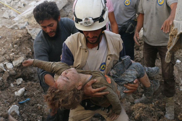 A man in a white helmet carrying a child