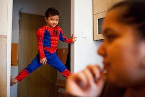 A boy in a costume climbs a door jamb