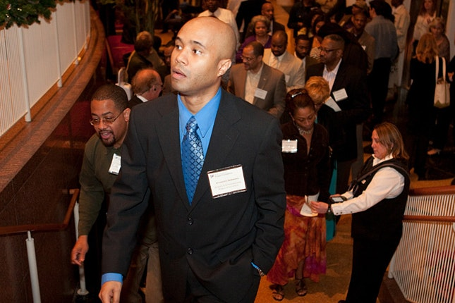 Anthony Simmons in suit, walking up stairs in crowded room