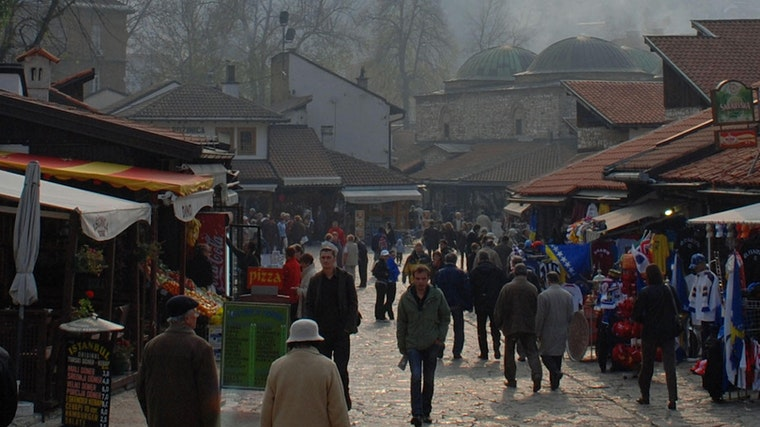 A crowd of people walking in a market