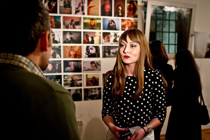 Ana Dragic in front of photos at her exhibit