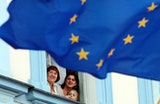 People looking out a window behind a European Union flag