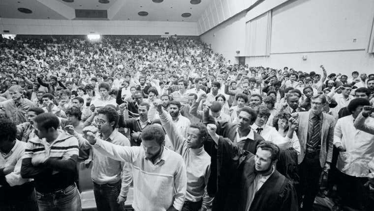 A hall full of students with their fists in the air