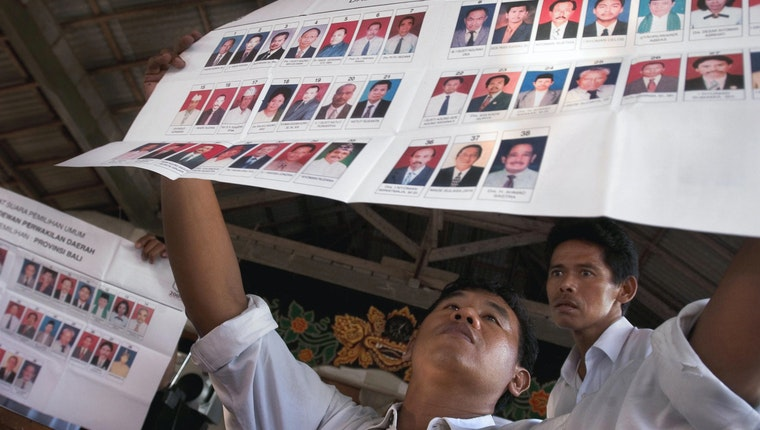 Men examining voting sheets with portraits