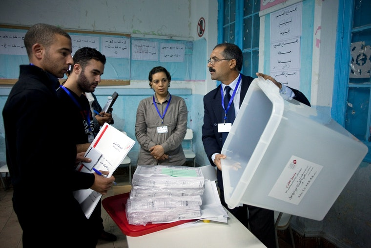 A polling station official in Tunis, Tunisia shows a ballot box to election observers.