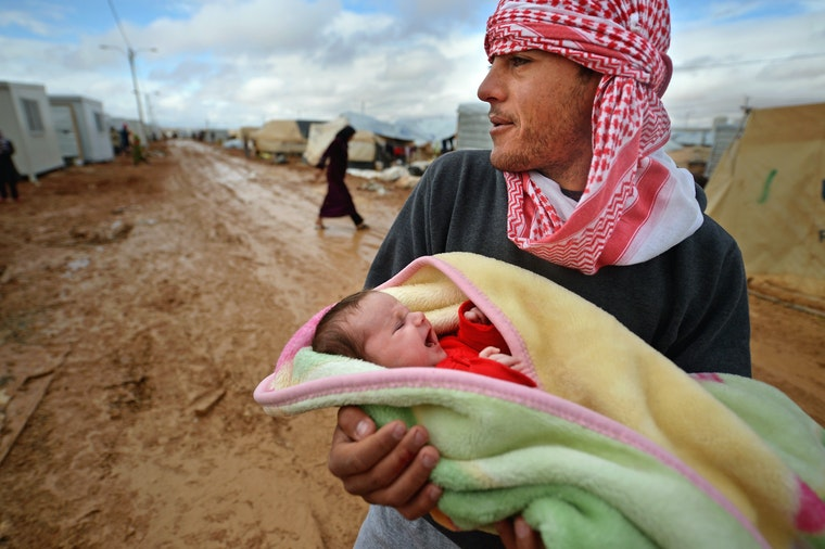 A man in a refugee camp holds a newborn.
