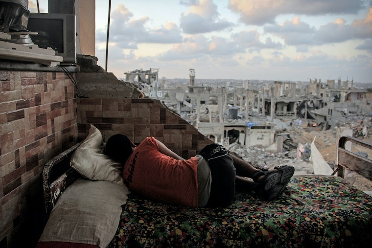 A young man sleeps in the ruins of a house near Gaza City that was shelled by the Israel Defense Forces.