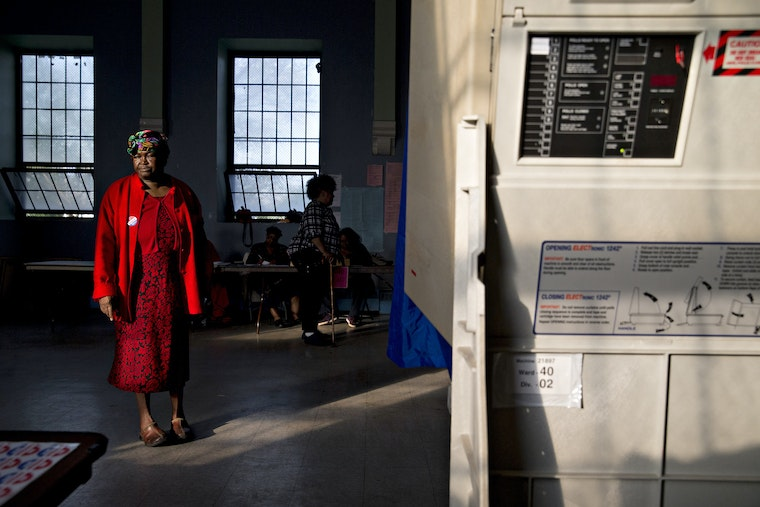 A woman stands in a room with a voting booth, waiting to cast her ballot.