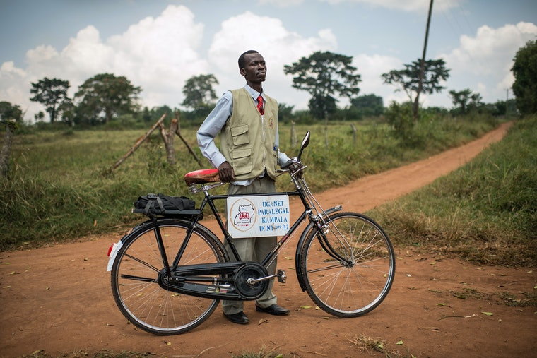 A man stands on the road with his bicycle.