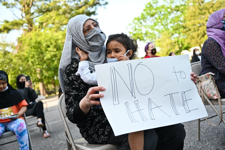 """A woman and child wearing protective face masks and holding a sign that reads """"no to hate"""""""