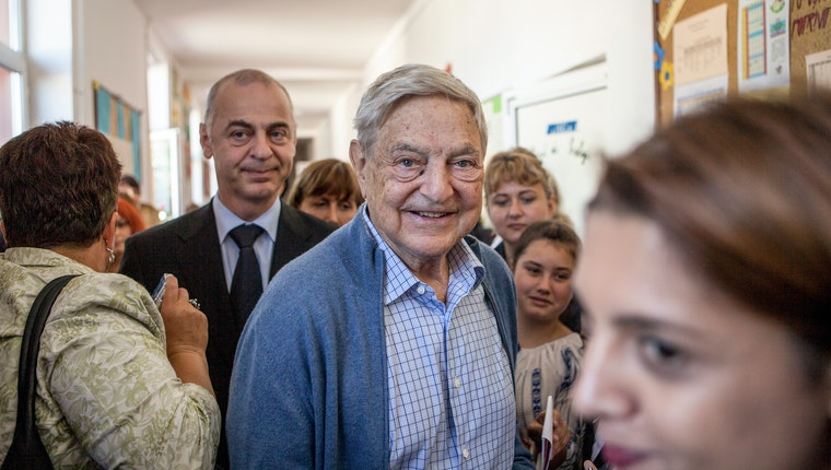 George Soros in a school hallway with a group of people