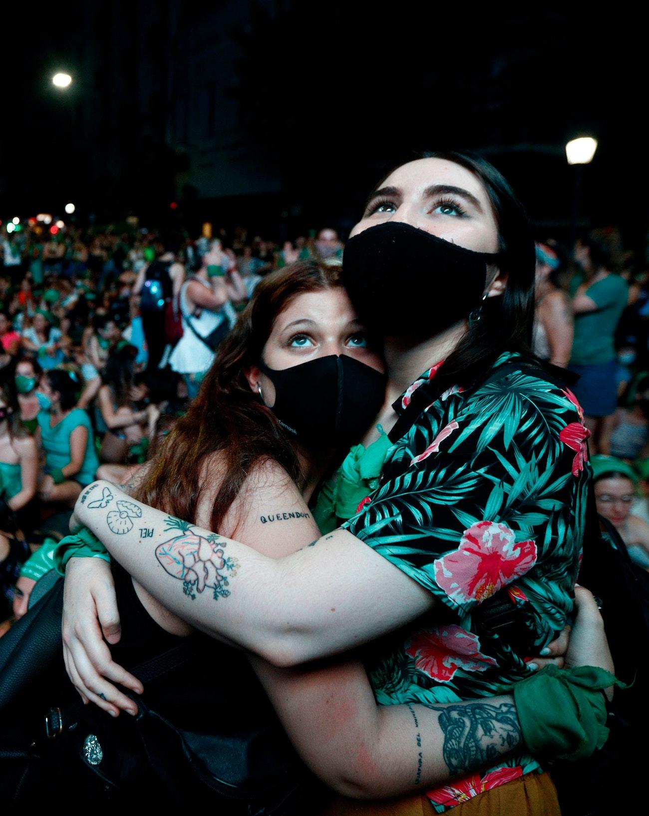 Two women wearing masks embracing among a large crowd
