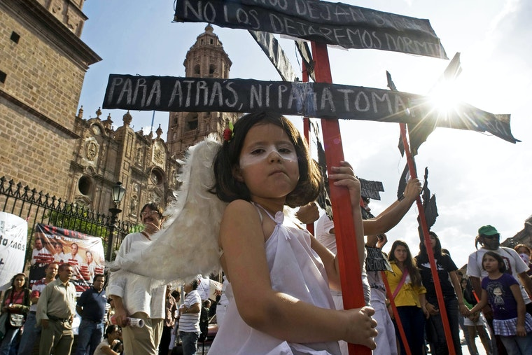 A young girl dressed as an angel looks at the camera during an antiviolence rally in Morelia, Mexico.