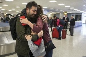 A family hugs at an airport baggage carousel