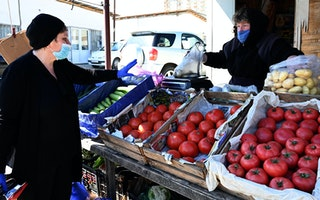 A woman buying vegetables at an outdoor market