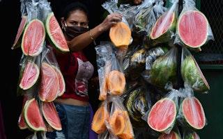 Un vendedor de frutas de pie junto a bolsas de fruta en rodajas